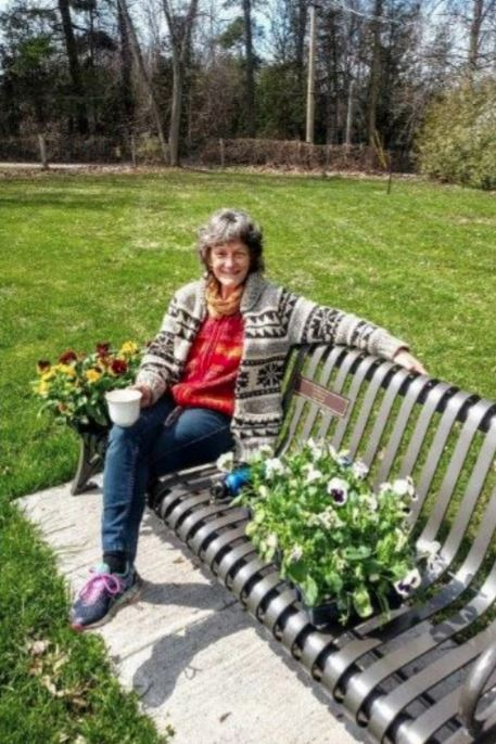 Woman sitting on a bench with a mug with flowers around her