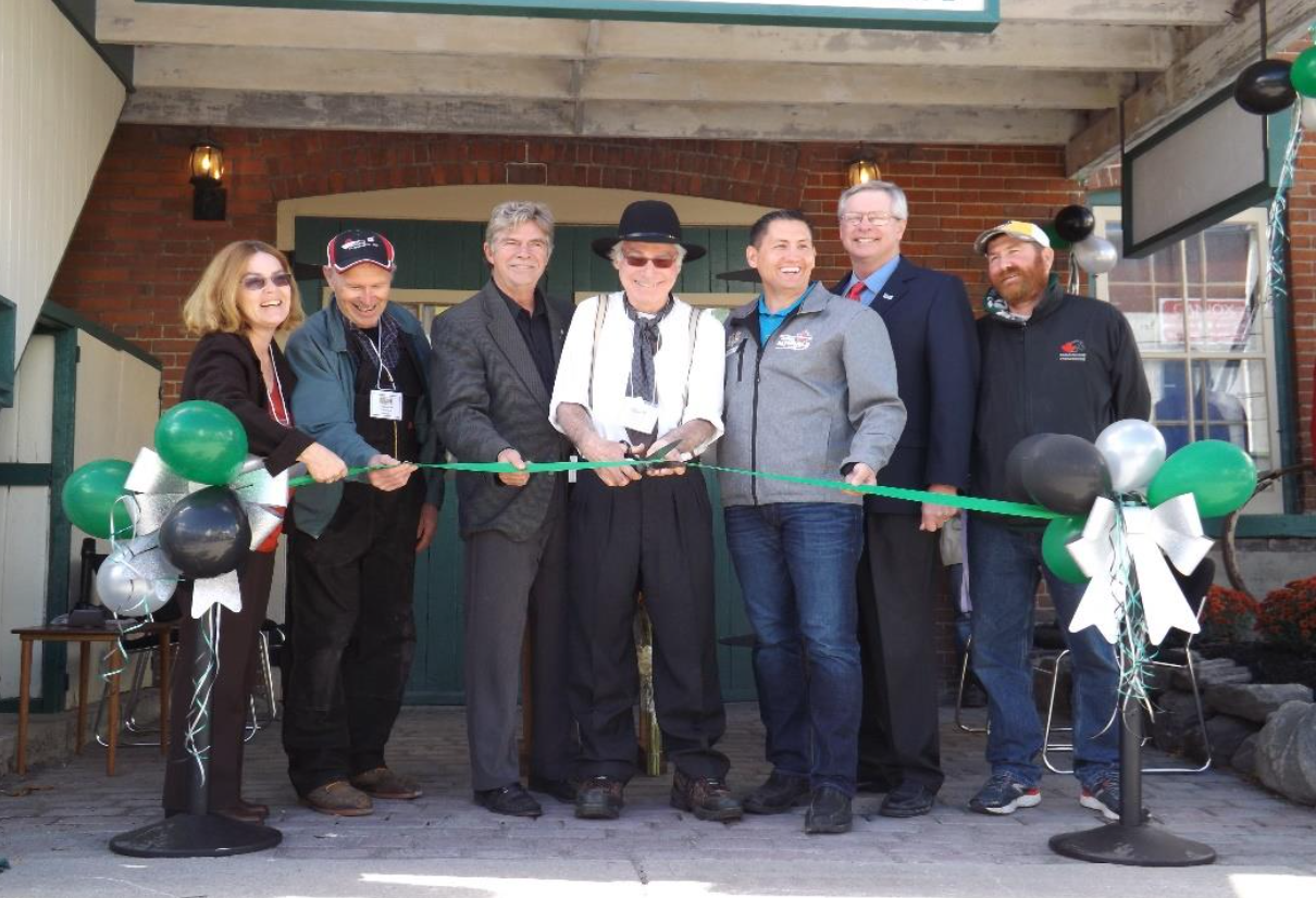 Group smiling while cutting a green ribbon in front of the historical building