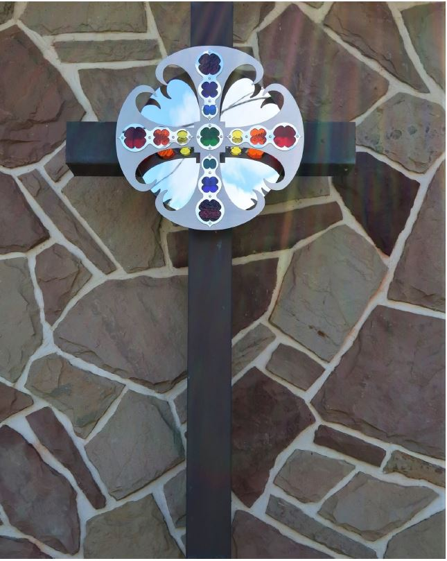 Cross with rainbow details added mounted on the Church